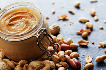 Peanut butter jar and heap of nuts on rustic background.