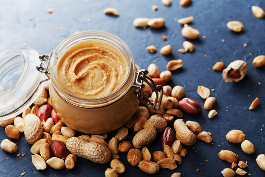 Peanut butter jar and heap of nuts on vintage background.