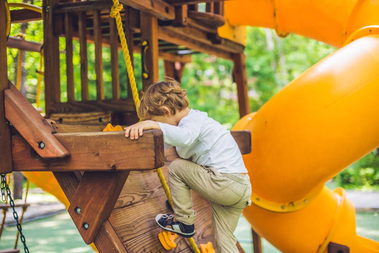 Cute little boy is playing on a wooden playground