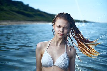 Beautiful young woman is resting on the sea, ocean, beach, water, vacation