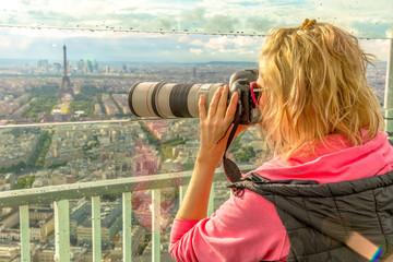 Traveler photographer takes photos of Tour Eiffel from observation deck of Tour Montparnasse. Woman photographer in French capital, Europe. Paris cityscape. Popular travel destination concept.
