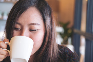 Closeup image of asian woman holding and drinking hot coffee with feeling good and smiley face