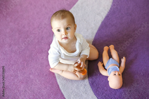 cute nice little baby girl sitting on purple carpet with doll