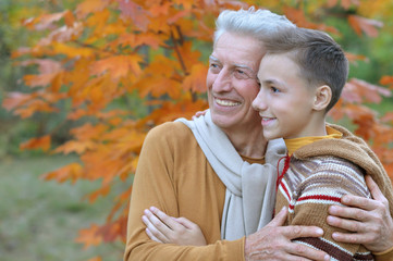 grandfather and grandson hugging  in park