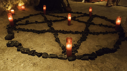 Satanic pentacle with lighted candles