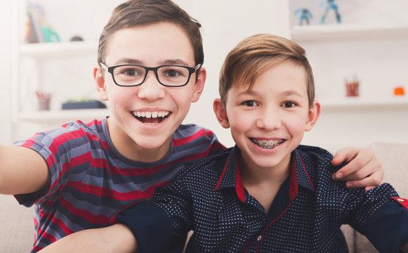 Two stylish smiling teens taking selfie