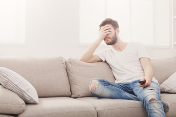 Young man watching television, using remote control
