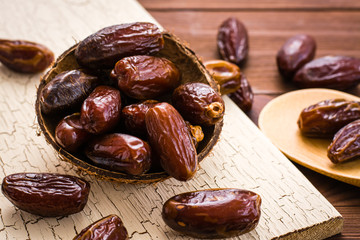 Sweet dried dates fruit in small wooden bowl on a shabby board