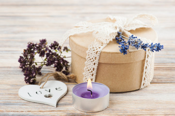 Gift with lace bow, lavender flower, lit candle