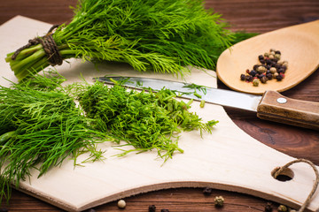 Chopped fresh dill on a cutting Board and a bunch of dill on a wooden table