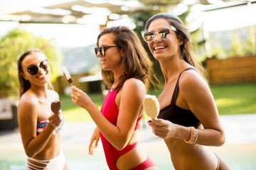 Pretty young women with ice creams by the swimming pool