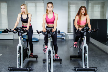 Young attractive girls do cardio training on a stationary bike at the gym