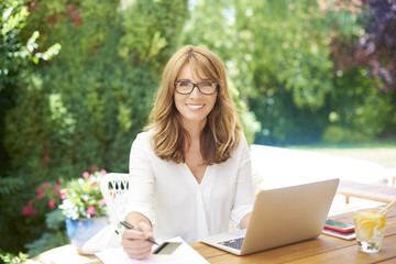 Online shopping is most comfortable. Shot of a middle aged happy woman using bank card and laptop while sitting on balcony at home and shopping online.