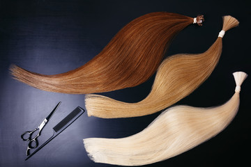 hair extensions of three colors on a dark background with Scissors and comb. copyspace top view.