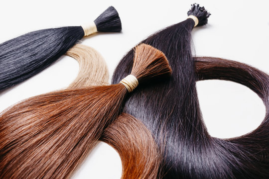 hair extensions of three colors on a white background. copyspace selective focus