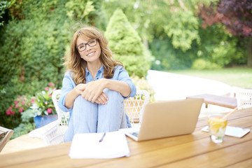 My perfect home office. Shot of a happy woman sitting on balcony while working on laptop at home.
