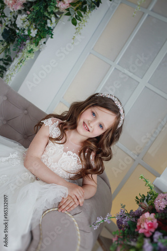 dfb4d03165f90 Beautiful little girl with curls and white Quinceanera dresses with a train  on the couch with