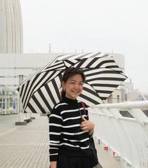 Asian woman in strip shirt with umbrella at YOKOHAMA, JAPAN