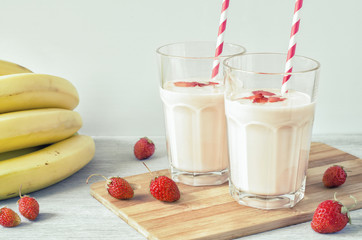 Two glasses of strawberry milkshake with a banana on a wooden board on a light background. Side view