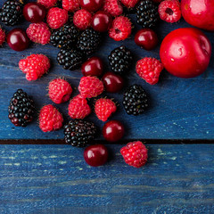 Food Background. Summer fresh berries on blue wooden table background. Copy space. Top view Vegetarian food - raspberry, blackberry and cherry. Rustic style