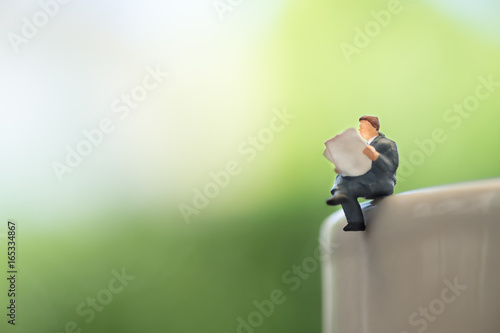 Reading, relaxing, hobby concept. Close up of businessman miniature reading newspaper on cup of hot coffee with green background.