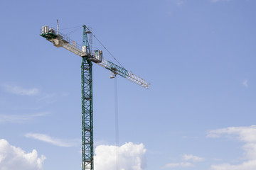 Green tower crane against the blue sky