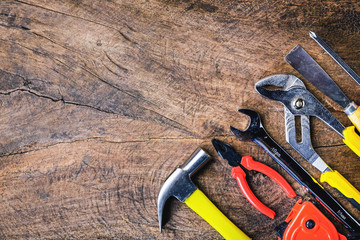 Foto op Textielframe Alpinisme Top view of Working tools,wrench,hammer,screwdriver,plier,electric drill,tape measure,machinist square on wooden rustic background. flat lay