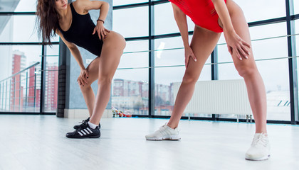 Cropped image of two beautiful female bodies wearing black and red swimsuits and trainers standing indoors