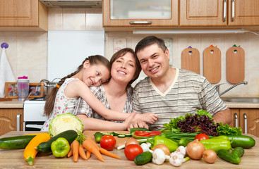family cooking in kitchen interior at home, fresh fruits and vegetables, healthy food concept, woman, man and children
