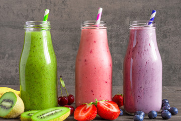 Colorful smoothie drinks in bottles with a straw and fresh fruits and berries