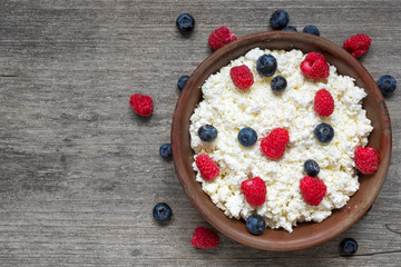 cottage cheese with fresh raspberries and blueberries in a bowl for healthy breakfast with ripe berries