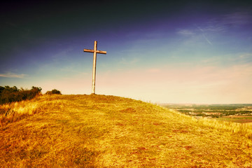 Big Christian cross standing on top of a hill Radobyl  in CHKO Ceske Stredohori area at evening in czech summer landscape