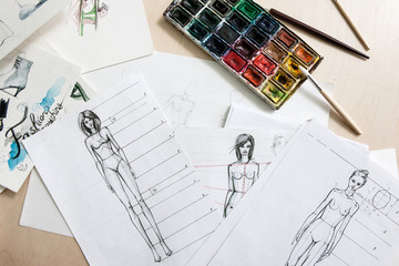 Designer fashion sketches of models with watercolor paint on desk