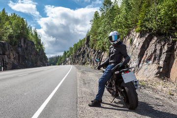 One motortraveler with own motorbike resting on roadside on the mountain asphalt road