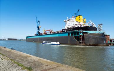 Barkasse auf der Hafenrundfahrt in Bremerhaven entlang eines Trockendocks mit Frachtschiff