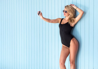 blonde woman in bodysuit with perfect body taking selfie smartphone