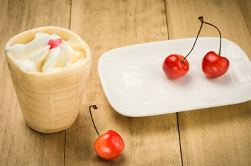 ice cream in a wafer cup and sweet cherry on a wooden background/ice cream in a wafer cup and cherry on a white saucer