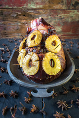 Festive Baked ham with pineapples and cloves in rustic setting