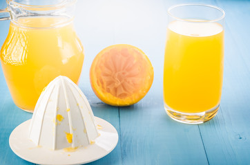 extractor and fresh orange juice in a glass/extractor and fresh orange juice in a glass on a wooden blue table