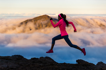 Fitness run athlete runner girl running at sunset on mountain trail. Scenic landscape cold clouds weather. Woman sprinting training cardio in nature outdoors.