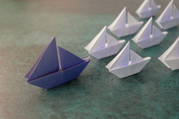 Origami paper sailboats, leadership concept, toning