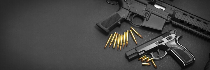 Handgun with rifle and ammunition on dark background with copy space