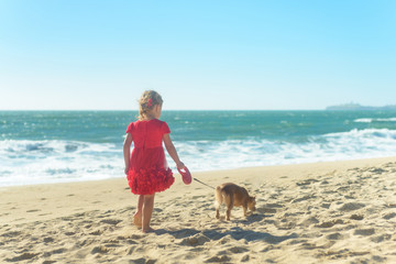 Little blond girl in red dress with dog on the beach