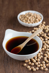 Soy sauce with Soy bean on wood table.