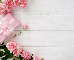 Bouquet of beautiful pink roses and gift in pink packing on white wooden background.Top view.Copy space