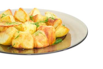 Fried potatoes with dill on dark glass dish closeup