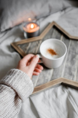 A girl in a sweater holds a cup of coffee on a designer wooden tray
