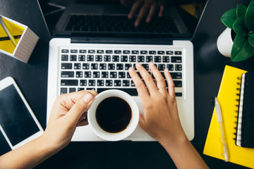 Holding coffee cup and typing keyboard in office