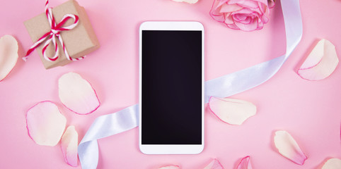 Mobile phone device with rose decoration on pastel pink background