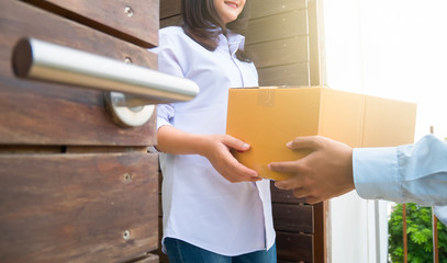 Close up hand of asia woman are receive a box from delivery man with sun light in delivery service concept.